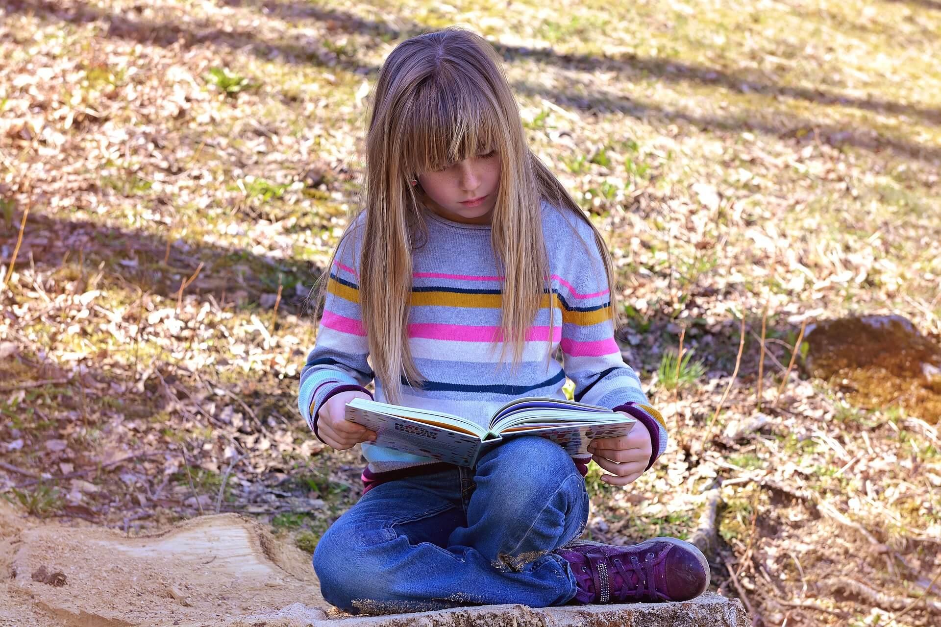 Mädchen liest ein Buch in der Natur - Lesepicknick